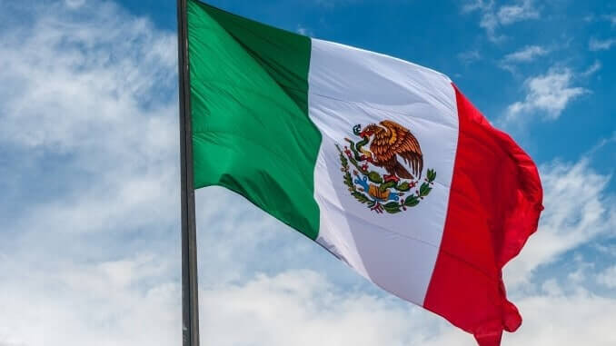 Flag of Mexico over blue cloudy sky