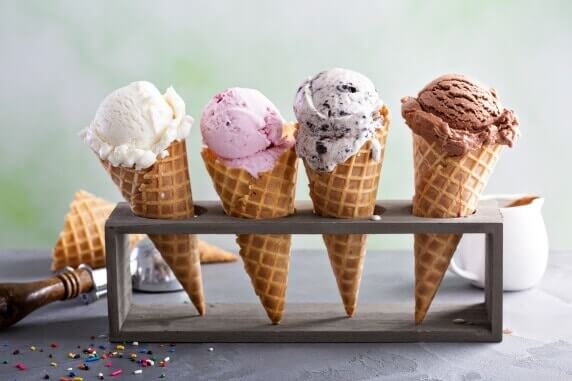 Variety of ice cream scoops in cones with chocolate, vanilla and strawberry
