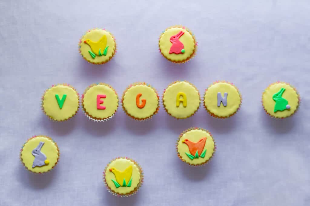 Pretty colorful yellow vegan Easter cupcakes with pastel icing shapes of Easter bunny rabbits and chicks and vegan word