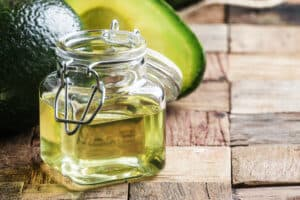 Avocado oil, old wooden background, selective focus